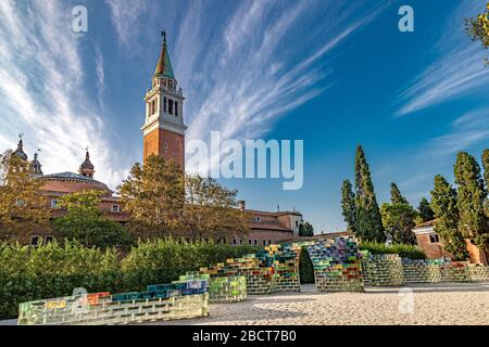 A curved wall of coloured glass blocks created by Pae White named Qwalala in front of The bell tower of San Giorgio Maggiore ,Venice ,Italy - Stock Photo
