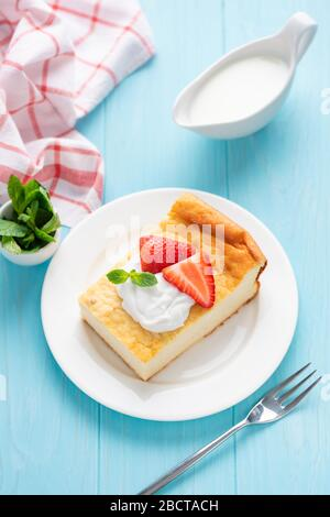 Cottage cheese casserole served with cream and fresh strawberries, blue wooden background, top view - Stock Photo
