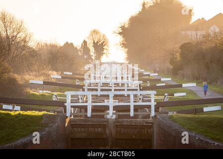 Caen Hill Locks, near Devizes, Wiltshire, UK. 23rd March 2020. On a crisp spring morning a runner makes her way along the Kennet and Avon Canal and pa - Stock Photo