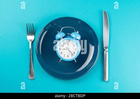 Alarm clock with fork and knife on the blue plate on blue table. Time to eat, Breakfast, Lunch Time and Dinner concept