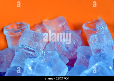 many pieces of ice of different shapes lie on an orange background. ice for coctails. ice for cooling alcoholic beverages - Stock Photo