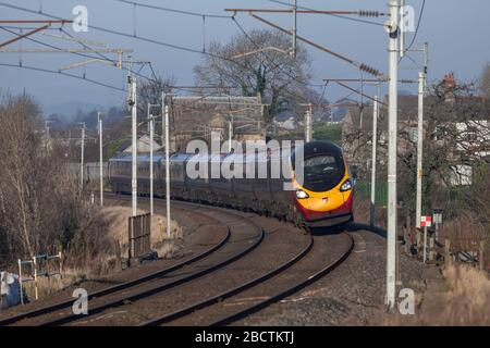 Virgin trains Alstom class 390 Pendolino tilting train tilting around a curve on the west coast mainline in Cumbria - Stock Photo