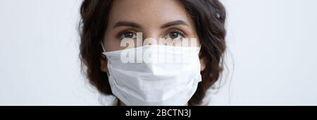 Young brunette woman doctor wearing protection medical mask. - Stock Photo