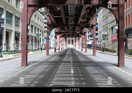 Nearly deserted Wabash Avenue in downtown Chicago with the elevated tracks above during the COVID-19 shelter-in-place order - Stock Photo