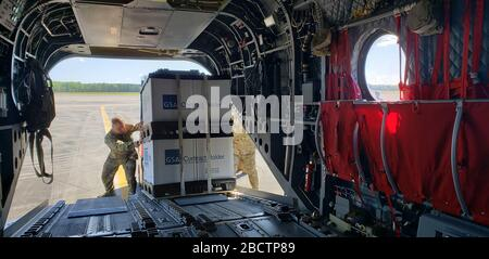 U.S. Army National Guard Soldiers with the South Carolina National Guard load personal protective equipment on a CH-47 Chinook assigned to the 2-238th General Support Aviation Battalion, South Carolina National Guard, to be transported and distributed to counties in the upstate of South Carolina in support of the South Carolina Department of Health and Environmental Control. The South Carolina National Guard remains ready to support the counties, local and state agencies, and first responders with requested resources for as long as needed in support of COVID-19 response efforts in the state. ( - Stock Photo