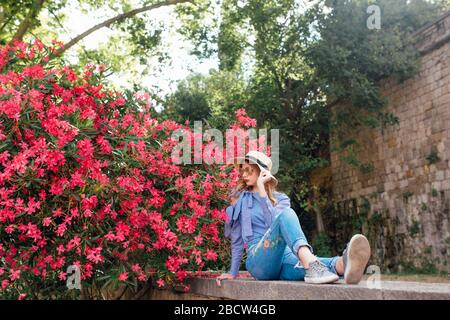 The girl next to the bushes with flowers in a hat and a stylish jacket. beautiful makeup - Stock Photo