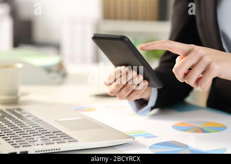 Close up of business woman hands checking smart phone on a desk at the office