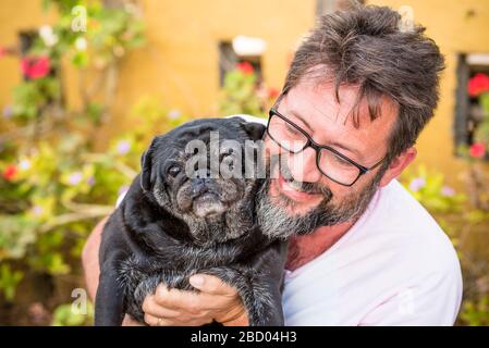 Outdoor nice portrait of adult caucasian man with black beard and same color old funny dog pug - garden in background and best friend love concept - Stock Photo