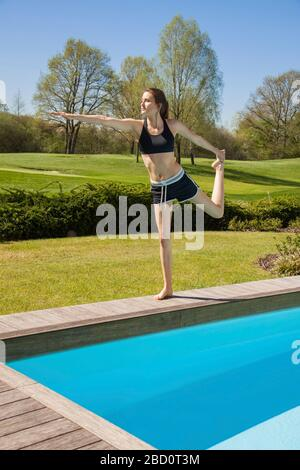 Pretty Healthy Girl Doing Standing Bow Pulling Yoga Pose Alone at the Poolside on a Sunny Morning. - Stock Photo