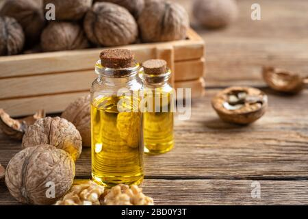 Essential oil of walnut on a wooden table. - Stock Photo