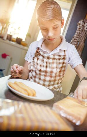 Boy in apron unpacking savoiardi biscuit cookies preparing tiramisu dessert. Stay at home and cook food background - Stock Photo