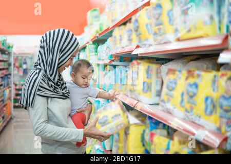 muslim asian mother buying baby product while carrying her daughter