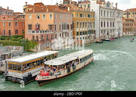 A route No 2 Vaporetto or water bus packed with passengers at the Accademia Vaporetto stop on The Grand Canal in Venice,Italy - Stock Photo