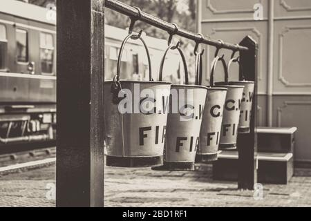 Black and white close up, vintage fire buckets hanging up in a row of four on the platform of vintage steam train station, Severn Valley Railway line. - Stock Photo