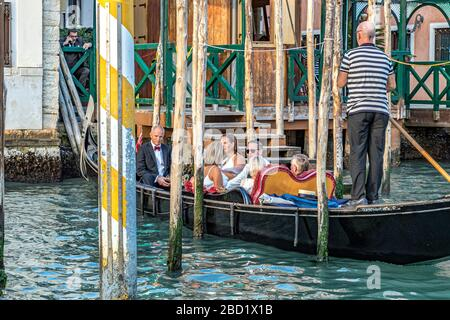 A wedding party taking a gondola ride along the Grand Canal , in Venice,Italy - Stock Photo