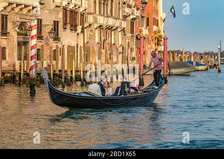 A wedding party taking a gondola ride in the late afternoon sunshine on The Grand Canal in Venice,Italy - Stock Photo