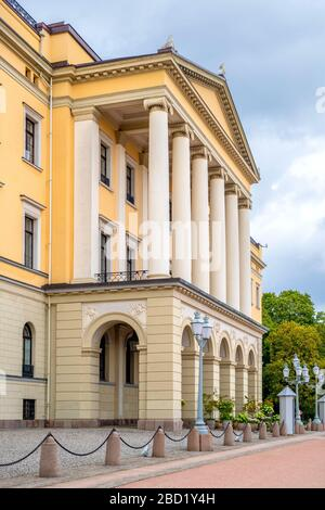 Oslo, Ostlandet / Norway - 2019/08/30: Facade of Oslo Royal Palace - Slottet - Bellevuehoyden hill seen from Slottsplassen square in historic center - Stock Photo