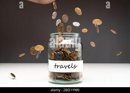 Coins in a jar with travels text on a white label. Money falling from the sky above. Savings abstract concept. Copy space.