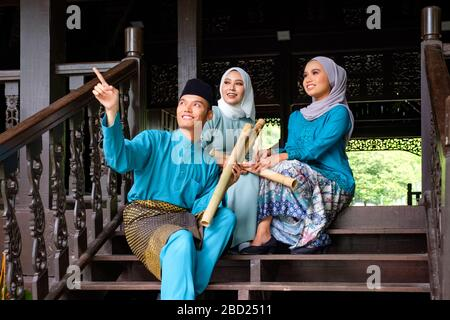 A group of three malay muslim people in traditional costume are having happy conversation during Aidilfitri celebration at terrace of traditional wood - Stock Photo