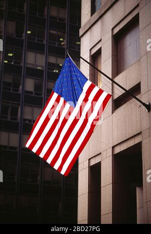 USA. New York. Manhattan. Stars and Stripes flag on building side flagpole. - Stock Photo