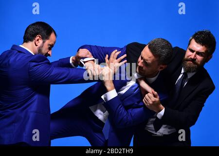 Business conflict and argument concept. Company leaders fight for business leadership. Coworkers decide upon best working position. Businessmen with strict faces in formal suits on blue background - Stock Photo