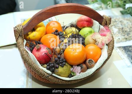 basket are pomegranates, dates, pears, quinces, mashed potatoes, black hawthorn. - Stock Photo