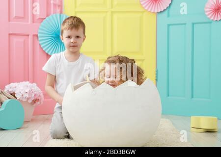 Pretty little blonde curly girl is sitting in a white egg and adorable blond boy portrait in white t-shirt on yellow, pink and blue background. Kid - Stock Photo