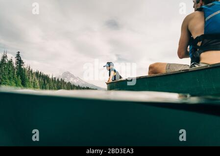 A young girl rides in a canoe with her dad on Lost Lake in Oregon. - Stock Photo
