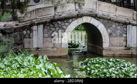 An amazing view of an old bridge inside a garden in China.