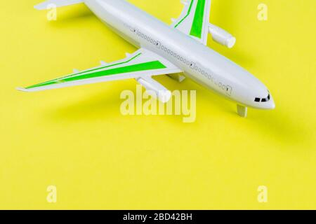 Miniature toy airplane on yellow background. Trip by airplane. - Stock Photo