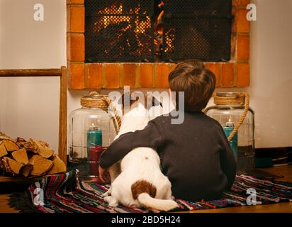 Bored child and dog staying at home during quarantine watching fire in fireplace - Stock Photo