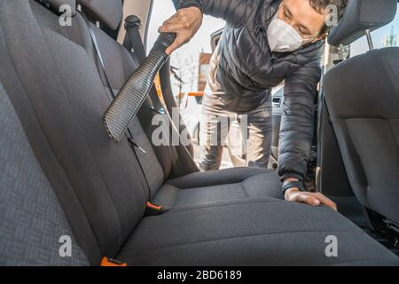 vacuuming the interior of a passenger car using an industrial vacuum cleaner. man works in protective medical mask. protection against coronavirus
