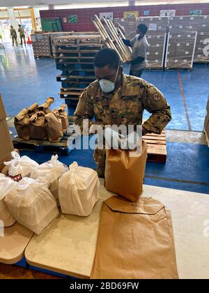 New York Army National Guard Spc. Standley Jean Baptiste, packages meals at the Bronx food distribution site in the Hunts Point Recreation Center April 6, 2020 in Bronx, New York. The meals are distributed to citizens who are quarantined and unable to leave their homes. - Stock Photo