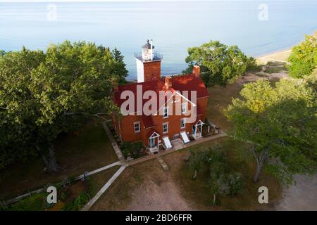 40 Mile point lighthouse tower Rogers City Michigan with a powerful light that is built on or near the shore to guide ships away from danger - Stock Photo