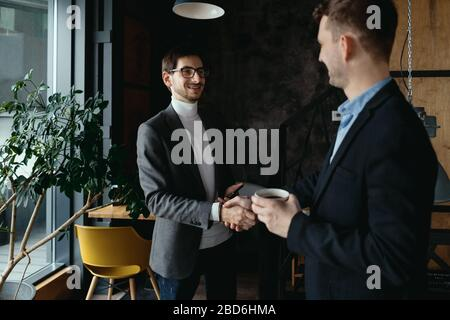 Smiling young business partners in business casual wear looking at each other while shaking hands after agreement. Greeting concept