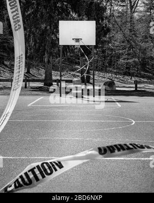 An outdoor basketball court stands closed to COVID-19 (Coronavirus). The basket is roped off by bright yellow caution tape and a pilon. From the view - Stock Photo