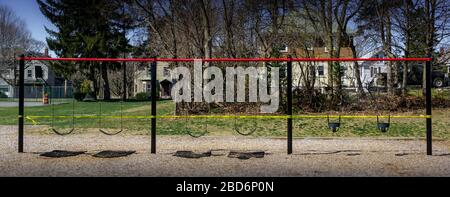 A row of children's swings is roped off with bright yellow caution tape preventing access. The entire playground has been closed due to the Corona (CO - Stock Photo
