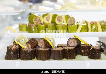 Tasty eggplant stuffed with rice, blurred zucchini stuffed with rice, slices cheese on background. Food on white plates concept. Turkish cuisine eggpl - Stock Photo