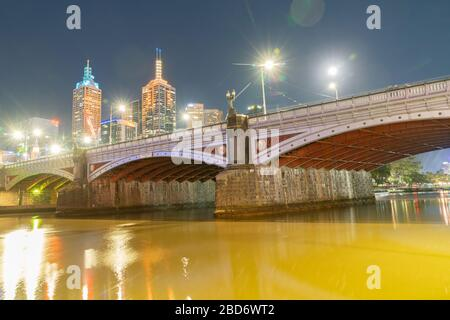 Melbourne Australia - March 9 2020; City at night, buildings, lights and reflections from below Princes Bridge on promenade.