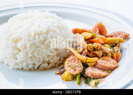 Asian spicy hot food or Thai food, closeup side view Thai sour pork or Nham fried with pepper and mixed vegetable with white cooked rice on round whit - Stock Photo