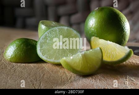 Slices of green Mexican lemons on an old cutting board and a Mexican basket in the background - Stock Photo