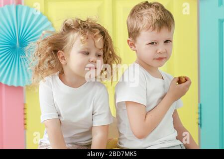 Pretty little blonde curly girl and adorable blond boy portrait in white t-shirt on yellow, pink and blue background. Kid gender relations concept. - Stock Photo