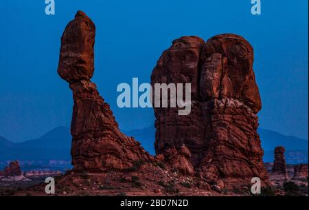 Balanced Rock in Arches National Park at dusk with the La Sal mountains in the background, Utah, USA.