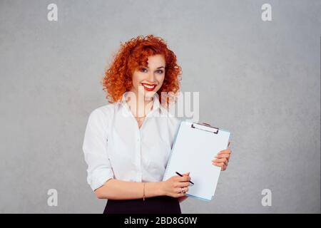 Woman, sign here. Portrait closeup beautiful young business girl secretary white shirt red head looking at you camera showing index finger on blank pa - Stock Photo
