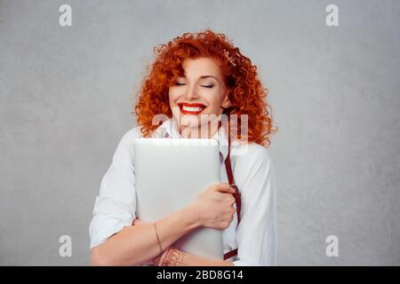 I love my laptop. Red head curly business woman in white shirt hugging computer smiling happy eyes closed isolated on gray background wall. - Stock Photo