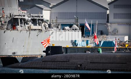 Japan Maritime Self-Defence Force submarines shares the dock with a US Navy Destroyer in the harbor at Yokosuka, Japan. - Stock Photo