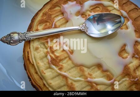 Confectioner a spoon greases the surfaceof condensed milk on the waffle cake - Stock Photo