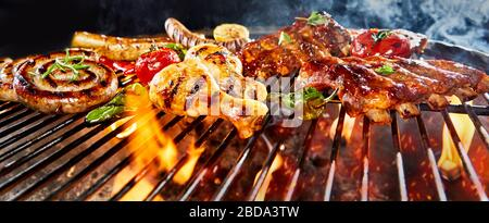 Panorama banner of assorted meat grilling on a BBQ in a low angle view with chicken legs, spicy pork ribs and sausages - Stock Photo