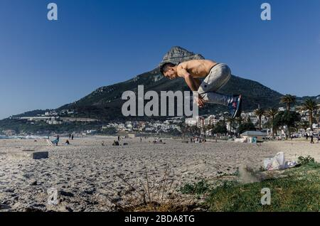 Young man on beach practicing somersaults and aerobics Camps Bay Cape Town South Africa - Stock Photo