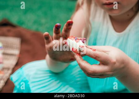 Cute little girl is painting Easter egg with her finger, cropped close up photo with targeted focus on the egg.